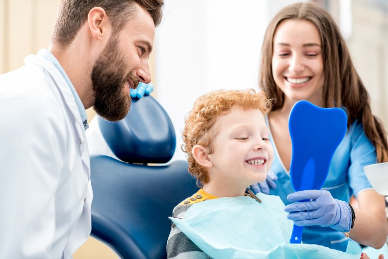 Son checking smile with mother and dentist watching